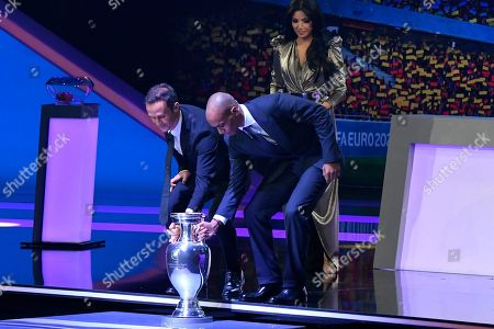 Stock Image of Portugal's former soccer player Ricardo Carvalho, left, and Portugal's 2016 European champion Joao Mario place the trophy on the stage before the draw for the UEFA Euro 2020 soccer tournament finals in Bucharest, Romania