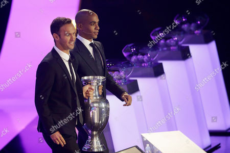 Portugal's former soccer player Ricardo Carvalho, left, and Portugal's 2016 European champion Joao Mario bring the trophy to the stage before the draw for the UEFA Euro 2020 soccer tournament finals in Bucharest, Romania