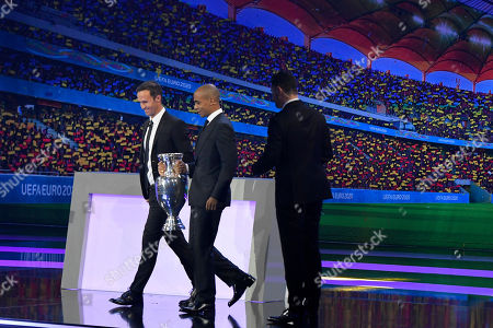 Stock Picture of Portugal's former soccer player Ricardo Carvalho, left, and Portugal's 2016 European champion Joao Mario bring the trophy to the stage before the draw for the UEFA Euro 2020 soccer tournament finals in Bucharest, Romania