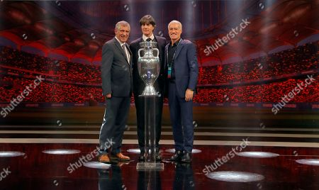 The coaches of Portugal Fernando Santos, left, Germany Joachim Loew and France Didier Deschamps who will play in group F, pose with the trophy after the draw for the UEFA Euro 2020 soccer tournament finals in Bucharest, Romania