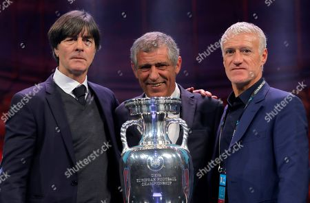 The coaches of Germany Joachim Loew, left, Portugal Fernando Santos, center, and France Didier Deschamps who will play in group F, pose with the trophy after the draw for the UEFA Euro 2020 soccer tournament finals in Bucharest, Romania