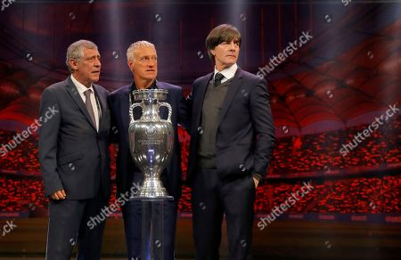 The coaches of Portugal Fernando Santos, left, France Didier Deschamps, center, and Germany Joachim Loew who will play in group F, pose with the trophy after the draw for the UEFA Euro 2020 soccer tournament finals in Bucharest, Romania