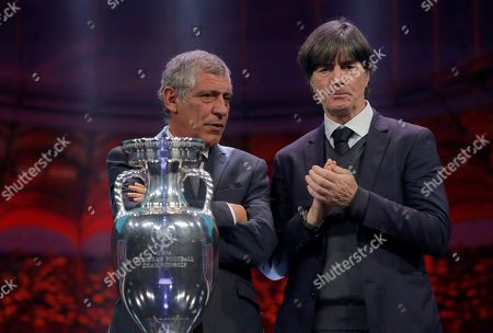 The coaches of Germany Joachim Loew, right, and Portugal Fernando Santos who will play in group F, pose with the trophy after the draw for the UEFA Euro 2020 soccer tournament finals in Bucharest, Romania