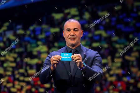 Netherland's former soccer player Ruud Gullit holds up the name Switzerland during the draw for the UEFA Euro 2020 soccer tournament finals in Bucharest, Romania