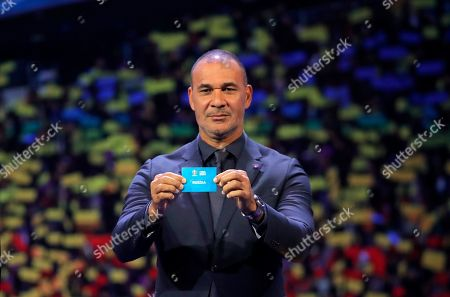 Netherland's former soccer player Ruud Gullit holds up the name Russia during the draw for the UEFA Euro 2020 soccer tournament finals in Bucharest, Romania