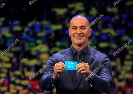 Netherland's former soccer player Ruud Gullit holds up the name Poland during the draw for the UEFA Euro 2020 soccer tournament finals in Bucharest, Romania