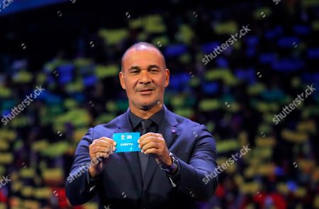 Netherland's former soccer player Ruud Gullit holds up the name Croatia during the draw for the UEFA Euro 2020 soccer tournament finals in Bucharest, Romania