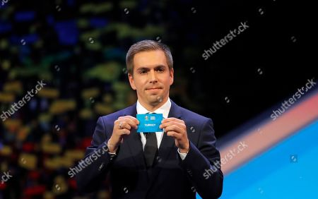 Germany's former soccer player Philipp Lahm holds up the name Turkey during the draw for the UEFA Euro 2020 soccer tournament finals in Bucharest, Romania