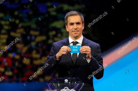 Germany's former soccer player Philipp Lahm holds up the name Austria during the draw for the UEFA Euro 2020 soccer tournament finals in Bucharest, Romania