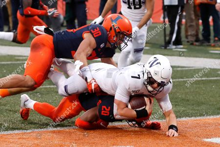 Stock Image of Andrew Marty, Nick Walker, Sydney Brown. Northwestern quarterback Andrew Marty (7) dives over Illinois defensive back Nick Walker (20) and past Sydney Brown (30) for a touchdown during the first half of an NCAA college football game, in Champaign, Ill