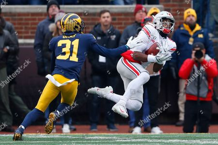 Ohio State wide receiver Garrett Wilson (5) catches a 47-yard pass as Michigan defensive back Vincent Gray (31) defends in the first half of an NCAA college football game in Ann Arbor, Mich