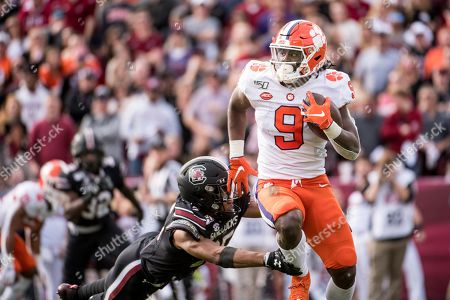 Stock Image of Clemson running back Travis Etienne (9) carries the ball against South Carolina's A.J. Turner during the first half of an NCAA college football game, in Columbia, S.C