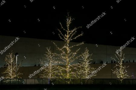 Stock Picture of People walk at the yard of the Stavros Niarchos Foundation Cultural Center during a Christmas tree lighting ceremony in Athens, Greece, on