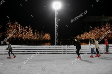 Stock Image of Youths skate on an ice rink at the Stavros Niarchos Foundation Cultural Center during a Christmas tree lighting ceremony in Athens, Greece, on