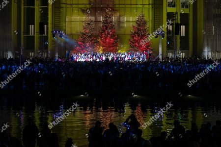 A choir performs during a Christmas tree lighting ceremony at the Stavros Niarchos Foundation Cultural Center in Athens, Greece, on