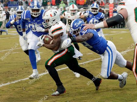Miami's Cam'Ron Harris (23) runs upfield against Duke defenders Trevon McSwain (95) and Tre Hornbuckle (59) during the first quarter of NCAA college football game in Durham, N.C