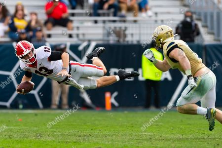 Georgia quarterback Stetson Bennett goes airborne while being chased by Georgia Tech linebacker David Curry during an NCAA college football game in Atlanta