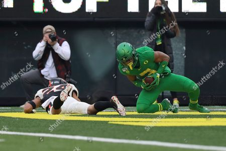 Oregon wide receiver Johnny Johnson III (3) recovers after scoring a touchdown, beside Oregon State defensive back David Morris (24) during the first half of an NCAA college football game in Eugene, Ore