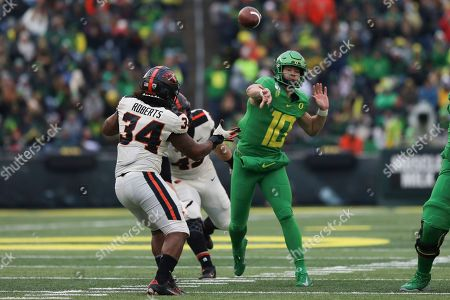 Oregon quarterback Justin Herbert (10) throws a pass away from Oregon State inside linebacker Avery Roberts (34) and defensive lineman Simon Sandberg (45) during the second half of an NCAA college football game in Eugene, Ore