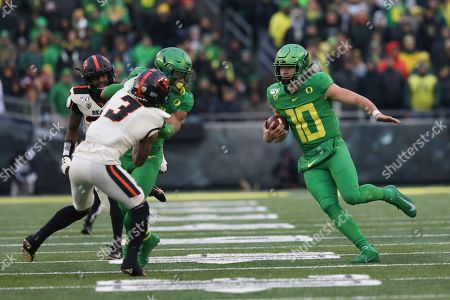 Oregon wide receiver Johnny Johnson III (3) tries to hold off Oregon State defensive backs Jaydon Grant (3) and Jalen Moore (33) to clear the way for Oregon quarterback Justin Herbert (10) during the second half of an NCAA college football game in Eugene, Ore