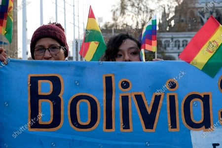 Stock Photo of Protesters hold banners, Bolivian and Wiphala flags during the rally. People gathered outside Downing Street to raise their voices against the coup in Bolivia and show their support to ousted president Evo Morales.