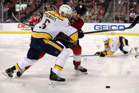 Dan Hamhuis, Brian Boyle. Nashville Predators defenseman Dan Hamhuis (5) and Florida Panthers center Brian Boyle fight for the puck during the second period of an NHL hockey game, in Sunrise, Fla