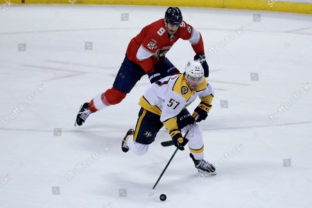 Dante Fabbro, Brian Boyle. Nashville Predators defenseman Dante Fabbro (57) skates with the puck as Florida Panthers center Brian Boyle (9) pursues during the third period of an NHL hockey game, in Sunrise, Fla. The Panthers won 3-0