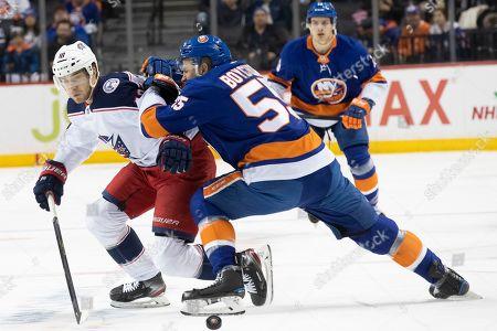 Alexander Wennberg, Johnny Boychuk. New York Islanders defenseman Johnny Boychuk (55) skates against Columbus Blue Jackets center Alexander Wennberg (10) during the first period of an NHL hockey game, in New York