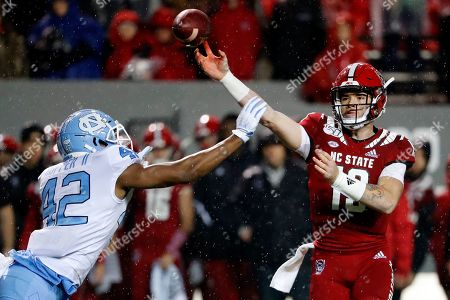 North Carolina State quarterback Devin Leary (13) is hurried on a throw by North Carolina's Tyrone Hopper (42) during the first half of an NCAA college football game in Raleigh, N.C
