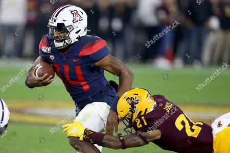 Arizona's Khalil Tate (14) slips the tackle of Arizona State's Jack Jones (21) during the first half of an NCAA college football game, in Tempe, Ariz