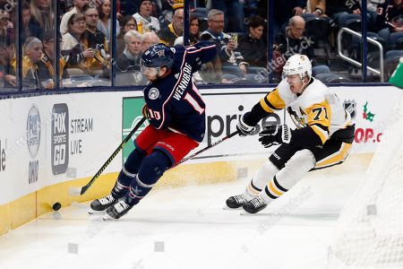 Columbus Blue Jackets forward Alexander Wennberg, left, of Sweden, passes in front of Pittsburgh Penguins forward Evgeni Malkin, of Russia, during an NHL hockey game in Columbus, Ohio, . The Blue Jackets won 5-2