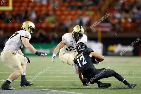 Hawaii quarterback Chevan Cordeiro (12) slides underneath Army linebacker Cole Christiansen (54), left, and Army defensive lineman Jacob Covington (57) during the first half of an NCAA college football game in Honolulu