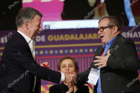 Colombian former president Juan Manuel Santos (L) and former leader of the Revolutionary Armed Forces of Colombia (FARC) Rodrigo Londono (R) shake hands during a forum during the Guadalajara International Book Fair in Guadalajara, Mexico, 30 November 2019.