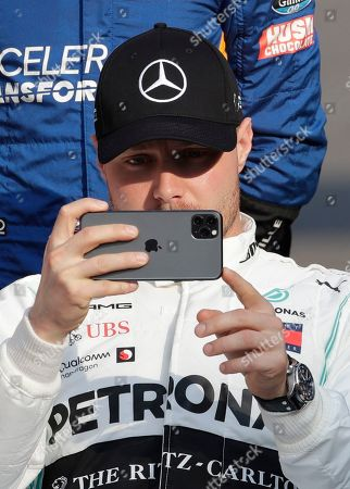 Mercedes driver Valtteri Bottas of Finland takes pictures during the end season driver's picture at the Emirates Formula One Grand Prix, at the Yas Marina racetrack in Abu Dhabi, United Arab Emirates, Sunday, Dec.1, 2019