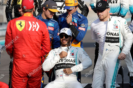 Mercedes driver Lewis Hamilton of Britain, right, looks to the Ferrari driver Sebastian Vettel of Germany, flanked by his teammate Valtteri Bottas of Finland, right, during the end season driver's picture at the Emirates Formula One Grand Prix, at the Yas Marina racetrack in Abu Dhabi, United Arab Emirates, Sunday, Dec.1, 2019