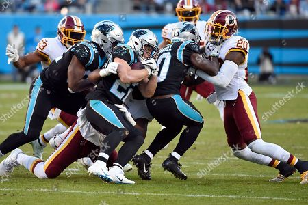 Carolina Panthers defensive tackle Stacy McGee, left, and wide receiver Curtis Samuel (10) block for running back Christian McCaffrey (22) against Washington Redskins strong safety Landon Collins (20) during the second half of an NFL football game in Charlotte, N.C