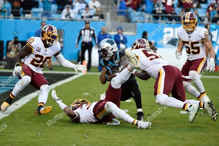 Washington Redskins free safety Montae Nicholson, inside linebacker Jon Bostic, right, and strong safety Landon Collins (20) stop Carolina Panthers wide receiver D.J. Moore (12) late in the second half of an NFL football game in Charlotte, N.C