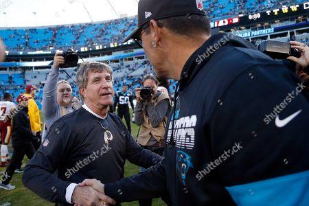 Washington Redskins head coach Bill Callahan and Carolina Panthers head coach Ron Rivera speak following an NFL football game in Charlotte, N.C