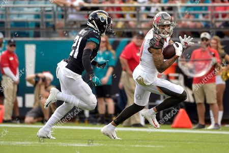 Tampa Bay Buccaneers wide receiver Mike Evans, right, runs past Jacksonville Jaguars cornerback A.J. Bouye after a reception during the first half of an NFL football game, in Jacksonville, Fla