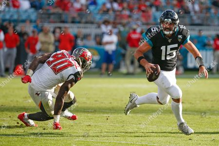Jacksonville Jaguars quarterback Gardner Minshew (15) scrambles away from Tampa Bay Buccaneers linebacker Jason Pierre-Paul (90) during the second half of an NFL football game, in Jacksonville, Fla