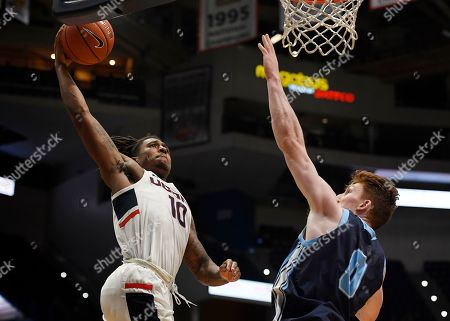Stock Photo of Connecticut's Brendan Adams, left, lines up a dunk as Maine's Andrew Fleming, right, defends during the second half of an NCAA college basketball game, in Hartford, Conn