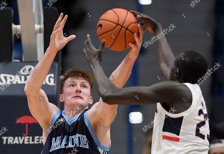 Stock Picture of Maine's Andrew Fleming grabs a rebound against Connecticut's Akok Akok, right, during the second half of an NCAA college basketball game, in Hartford, Conn