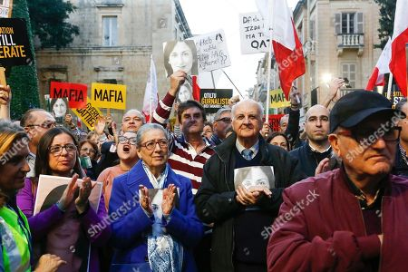 Rose Vella, center left, mother of late Daphne Caruana Galizia, and father of Daphne, Michael Vella, attend a protest in La Valletta, Malta, . Malta's embattled prime minister has received a pledge of confidence from Labor Party lawmakers amid demands for his resignation by citizens angry over alleged links of his former top aide to the car bomb killing of a Maltese anti-corruption journalist. Hours later, thousands of Maltese protested outside a courthouse demanding that Joseph Muscat step down
