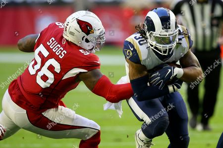 Los Angeles Rams running back Todd Gurley (30) runs as Arizona Cardinals outside linebacker Terrell Suggs (56) makes the tackle during the first half of an NFL football game, in Glendale, Ariz