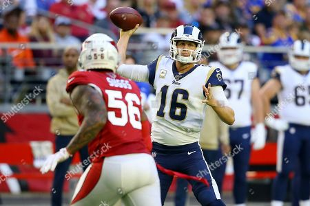 Los Angeles Rams quarterback Jared Goff (16) throws as Arizona Cardinals outside linebacker Terrell Suggs (56) looks on during the first half of an NFL football game, in Glendale, Ariz