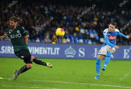 Napoli's Polish midfielder Piotr Zielinski (R) kicks the ball next to Bologna's Italian midfielder Andrea Poli during the Italian Serie A football match SSC Napoli vs Bologna FC 1909.