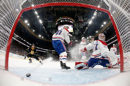 With a wide angle lens, Montreal Canadiens goaltender Carey Price looks behind him as the puck goes across the crease but not in as Boston Bruins' Sean Kuraly, left, moves in during the second period of an NHL hockey game, in Boston