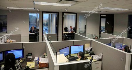 Stock Photo of At the law firm of Slater, Slater and Schulman, shows lawyers Linc Leder, top left, and Michael Werner, top right, in their offices, while paralegals work in their cubicles, in Melville, N.Y. Attorney Adam Slater said since New York state opened its one-year window allowing sex abuse suits with no statute of limitations, his firm has signed up nearly 300 new clients and hired a half-dozen new paralegals to field calls