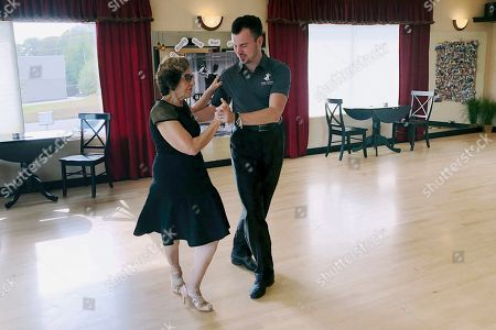 Dance instructor Ned Pavlovic, a native of Serbia, teaches his student Rouhy Yazdani, a native of Iran who now lives in Milford, Conn., some ballroom dance moves at the Fred Astaire Dance studio in Orange, Conn. Owners of Ballroom dance studios including the Fred Astaire studio say the immigration clampdown has made it even more difficult to find qualified instructors. The small business owners, U.S. dance studio chains and immigration attorneys say there's greater backlogs for visa applications and an overall increase in evidence requests, including for redundant and unnecessary documents