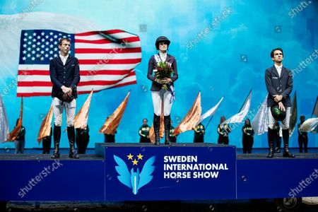 Silver medalist Harrie Smolders (NED) gold winner Jessica Springsteen (USA) and bronze medalist Marlon Modolo Zanotelli (BRA) on the podium after Sunday's grand prix jumping competition